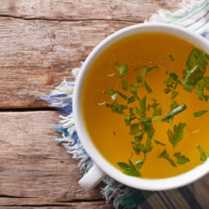 Tasty meat broth with parsley in a white bowl closeup. horizontal view from above