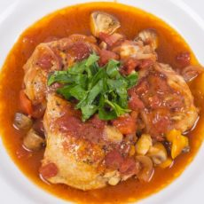 Chicken cooked in tomato based sauce with red bell peppers and mushrooms, garnished with Italian flat leaf parsley.